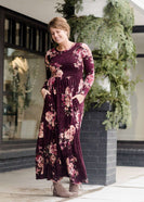 Woman wearing a burgandy floral maxi dress with sole society boots