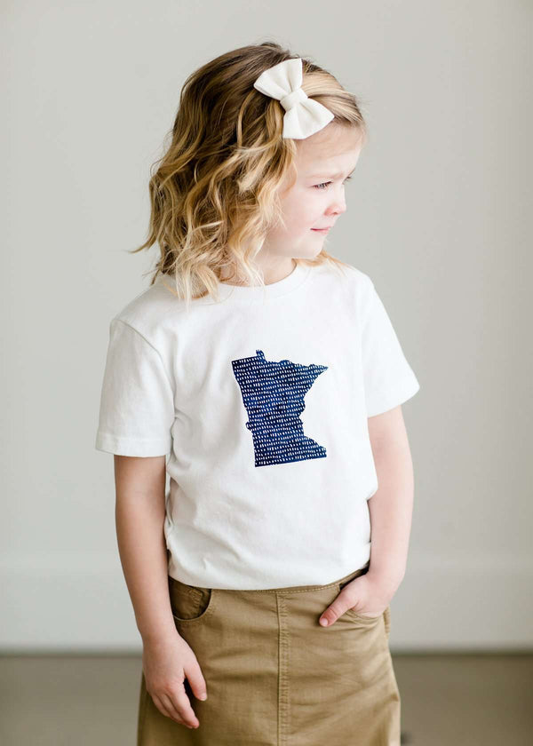 Inherit Co.  | Minnesota Made Toddler Tee | Toddler girl wearing a white minnesota logo on a white tee shirt. She is also wearing a long khaki skirt.