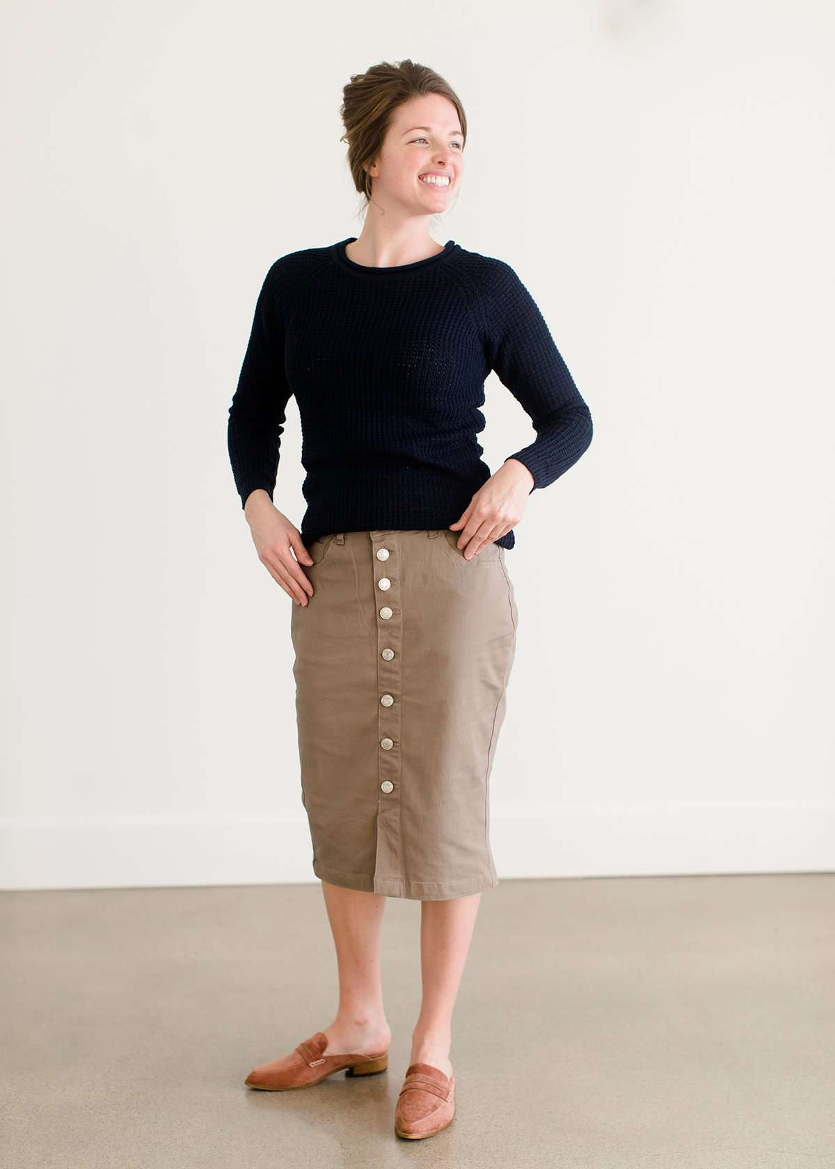 Woman wearing a khaki midi length skirt with faux buttons running down the front. It is paired with a navy sweater and copper, suede slide shoes.