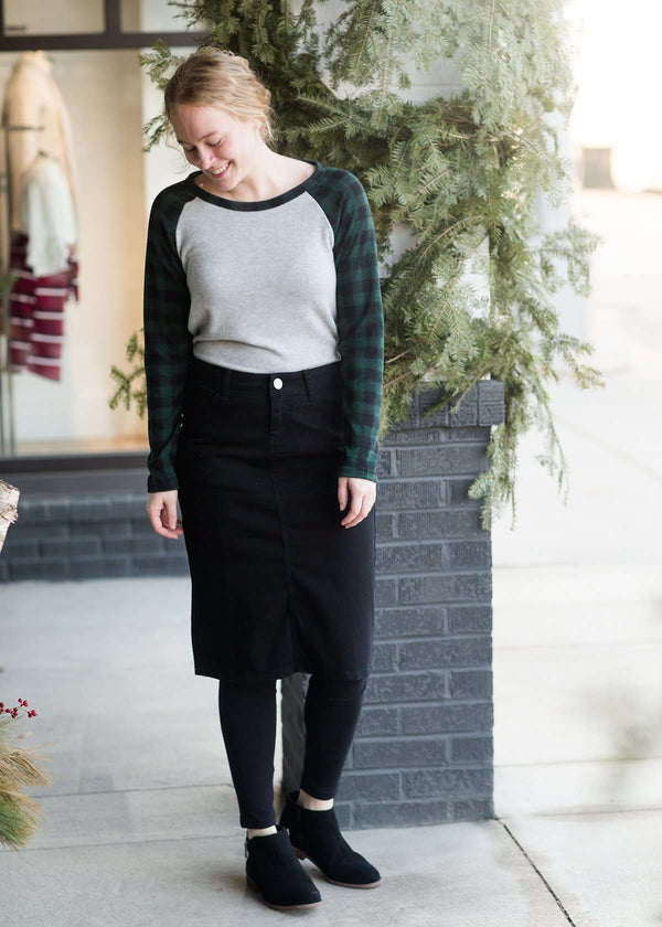 Inherit Co.  | Remi Black Midi Skirt | Woman wearing a black below the knee denim midi skirt.