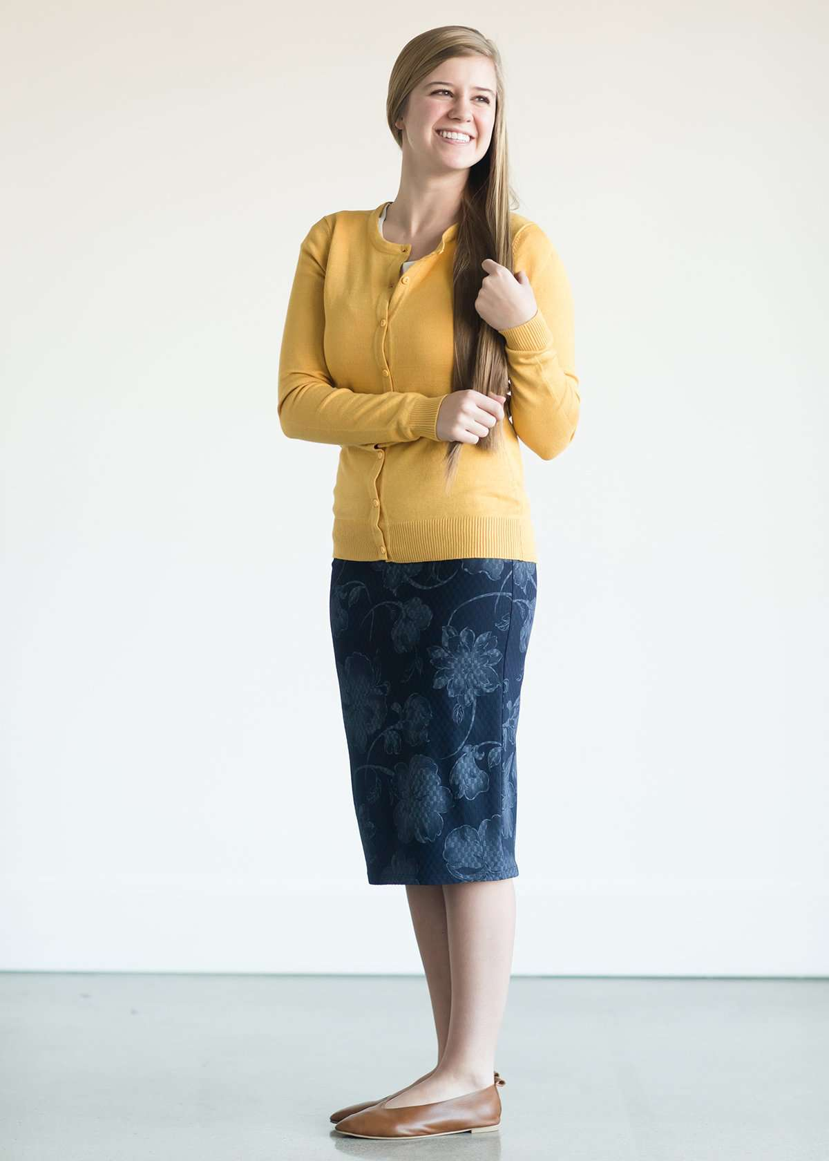 Woman wearing a navy below the knee stretch skirt with muted florals woven in it.