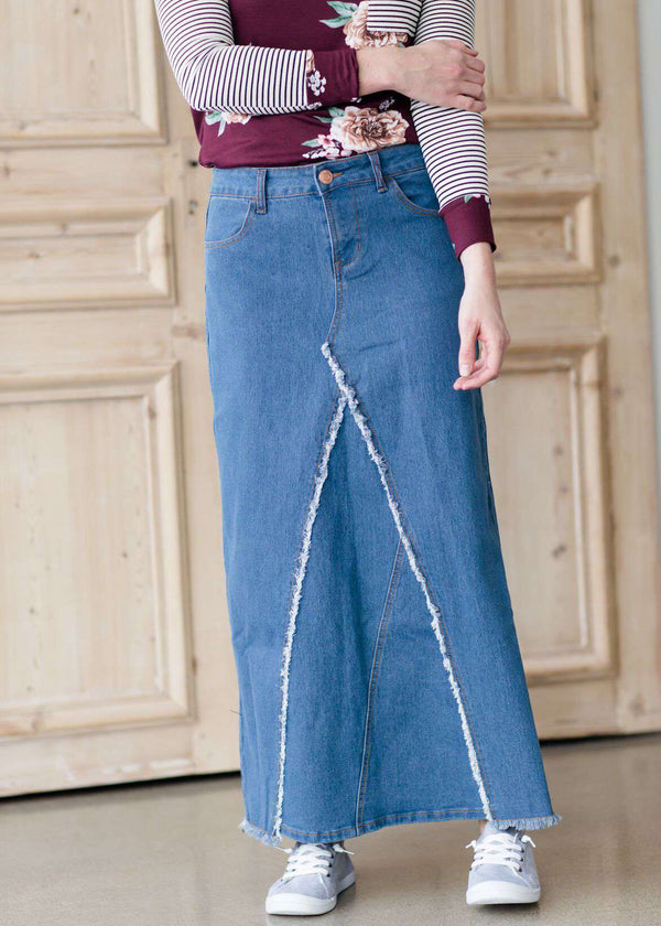 c818696d4 woman wearing an a-line modest long denim skirt with fringe detail and no  slit