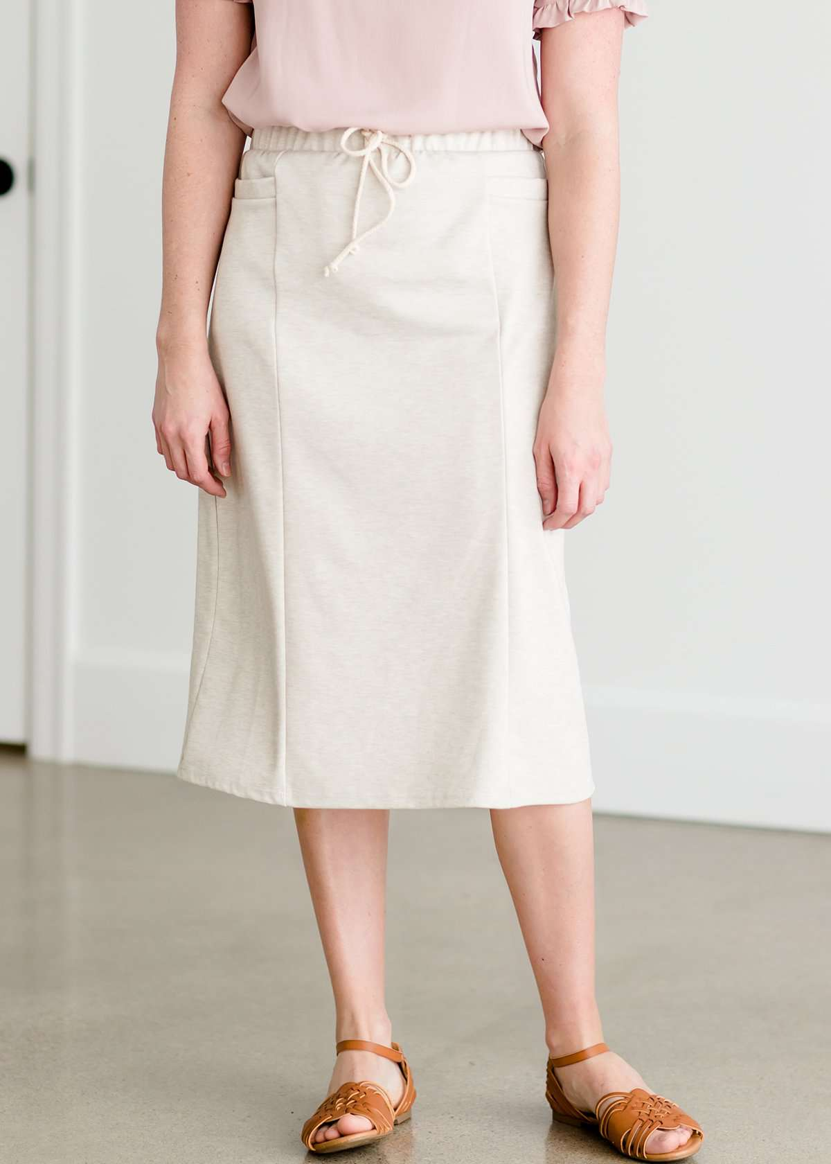 Woman wearing a cream colored french terry below the knee skirt with front ties, front panels and pockets!