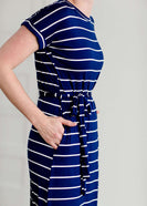 Woman wearing a modest navy and white stripe maxi dress that has cap sleeves and a fabric belt that is detachable!