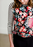 Tween wearing a floral and black striped top with a rose gold sequin pocket with a black maxi skirt