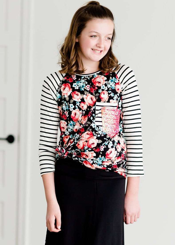 664d117c2ef55a Tween wearing a floral and black striped top with a rose gold sequin pocket  with a