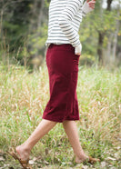 Woman wearing a below the knee corduroy skirt. This skirt is a fin corduroy with a gold button snap, no slit and no back pockets. It comes in burgundy, teal, burnt orange and dark khaki.
