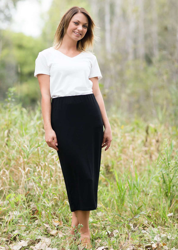 Woman wearing a straight style, ultra soft versatile black midi skirt.