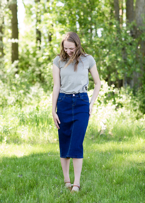 Woman wearing a dark denim below the knee jean skirt.