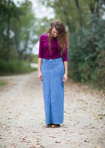 Woman on a gravel road wearing a long denim modest jean skirt