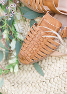 genuine braided leather strappy front sandal with closed toe and open back. 1 inch heel and pretty buckle accent.