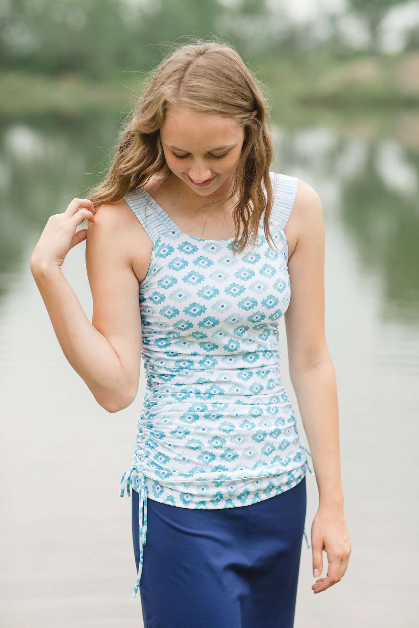 Teen girl wearing modest teal and white design long swim suit top with side cinch.