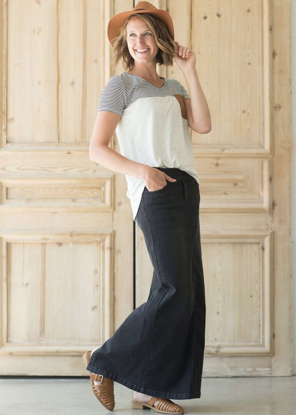Woman wearing a modest long black denim skirt with pockets