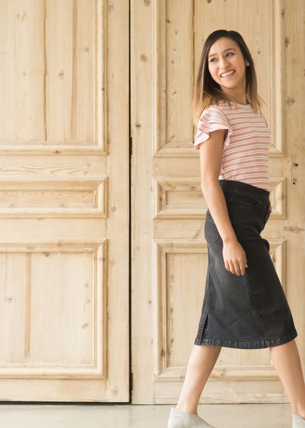 Woman wearing a modest black denim skirt that falls below the knee