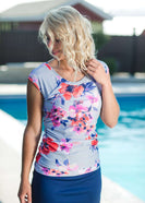 Woman by pool wearing a gray and floral modest swimsuit top