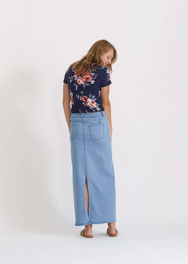 Woman wearing a long denim jean skirt that has a dark wash and a light wash. this is a long modest jean skirt.