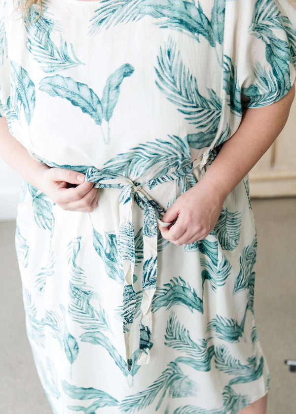 Woman wearing a modest plus size green feather print dress