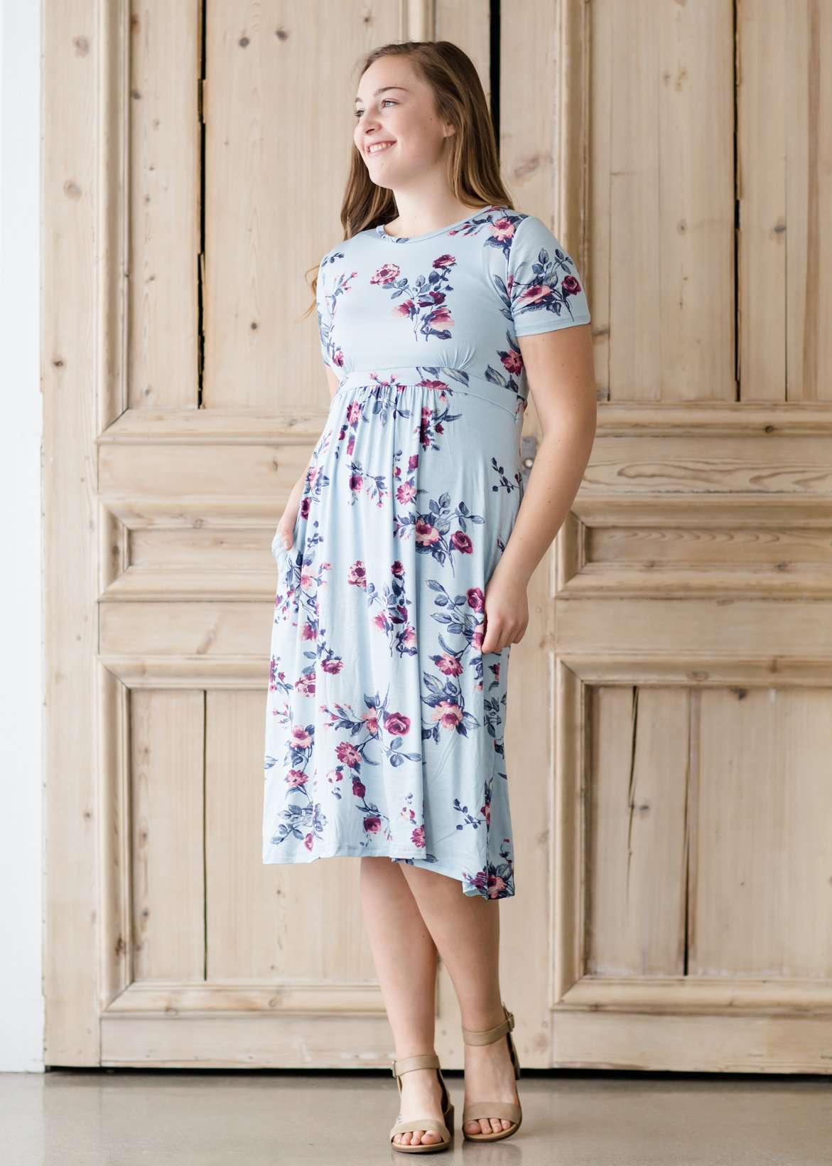 Woman wearing a light blue modest empire waist midi dress with flowers on it