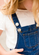 young girl in overall denim jumper dress