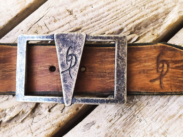a Ishaor original buckle square buckle with a triangle in the center and Ishaor logo on it ,stunning buckle that will upgrade any belt