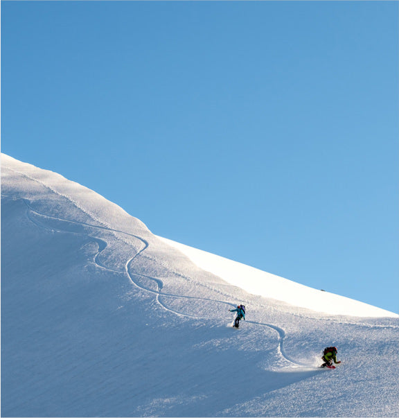 Two snowboarders riding down a snowy mountain.