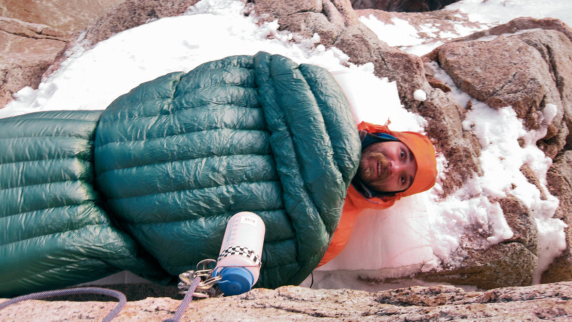 A downward-angled shot of Andrew Rothner in an R1® and a sleeping bag, lying on the side of a mountain. His eyes are wide, expressing shock.