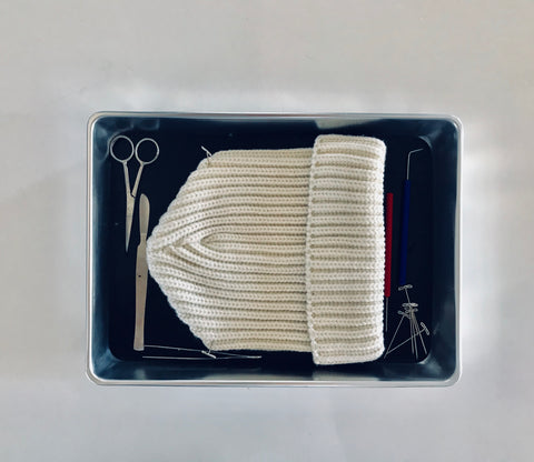 cream colored hat o na tray with shears and other tools