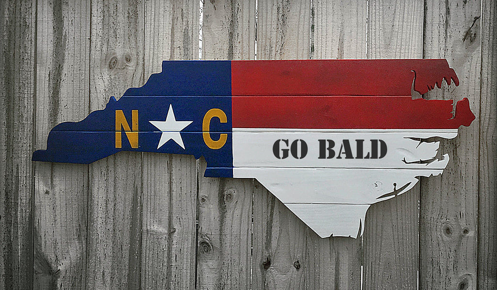 rustic cut out of the state of north carolina mounted on barnwood wall with go bald stenciled on it