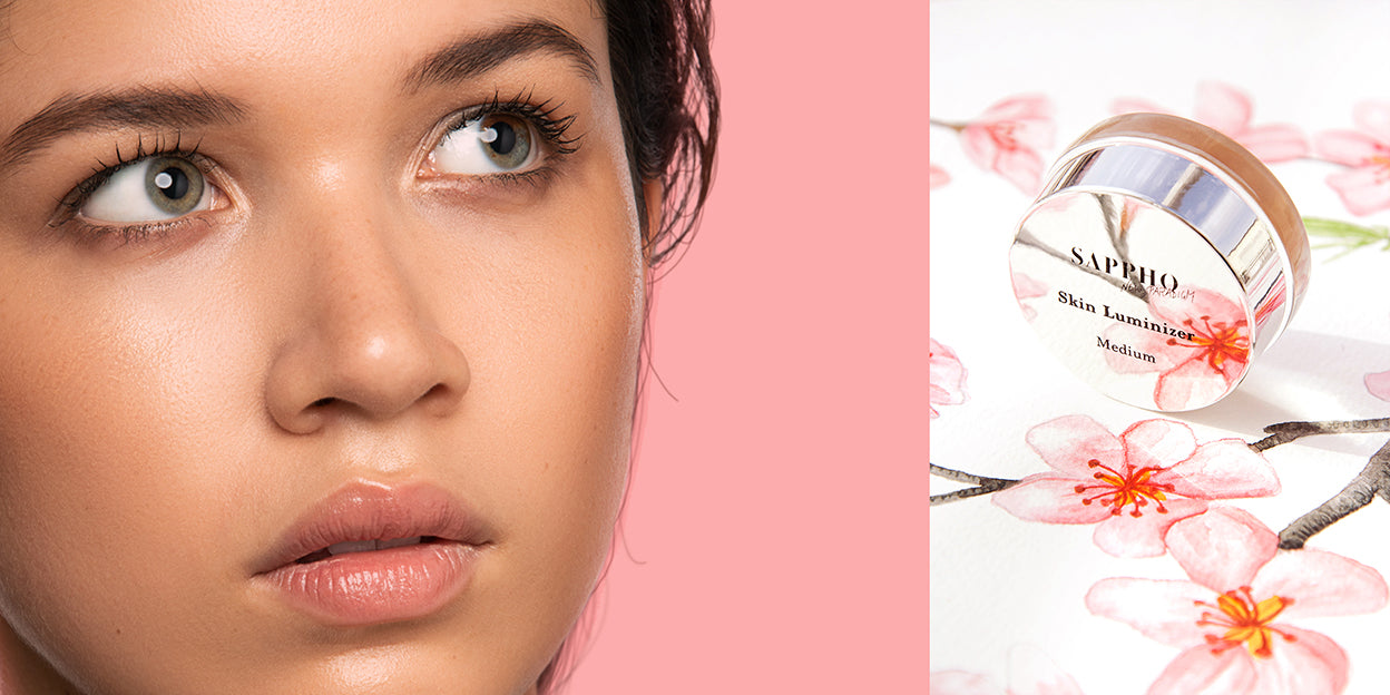 Spring banner with latina model wearing all natural makeup look and dyptique closeup of vegan Skin Luminizer on painted cherry blossoms