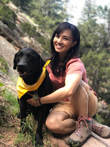 International Certified Yoga Trainer Heidi Chen with her dog on a mountain, taking a break while hiking