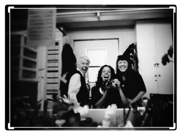 Jennifer Beals holding camera with JoAnn Fowler and Cynthia Summers laughing looking at mirror in black & white photo