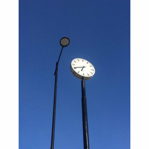 Blue sky with a lamp post and a station clock. Photo by Niki Fulton