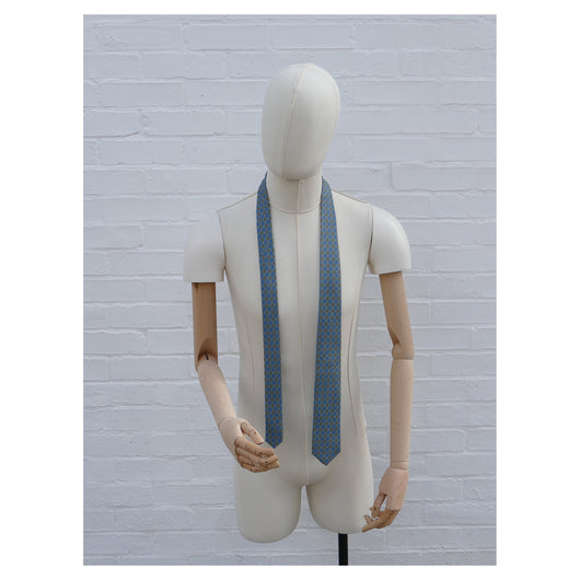 Lovewell Khaki silk tie designed by Niki Fulton. A teal & khaki print. Seen here on a mannequin.