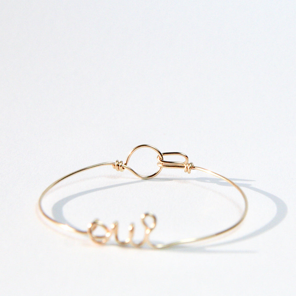 Personalised Oui name wire bangle bracelet in Yellow Gold handmade by Rachel and Joseph jewellery UK