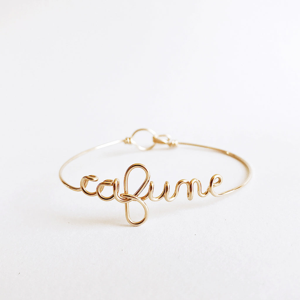 Personalised Cafune name wire bangle bracelet in Yellow Gold handmade by Rachel and Joseph jewellery UK
