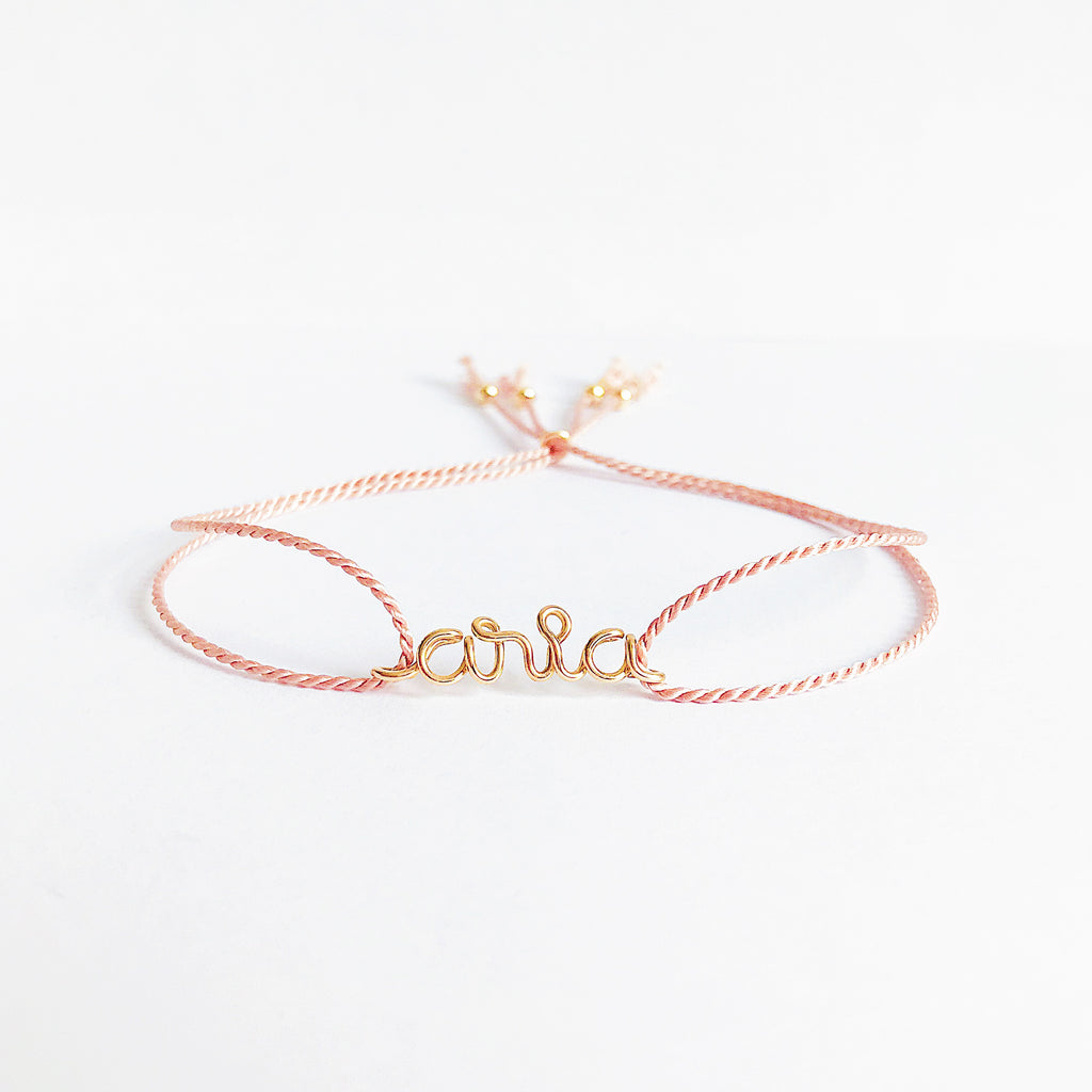 Personalised name Aria wire Light Pink natural Silk bracelet in 14K yellow gold filled handmade by Rachel and Joseph Jewellery in London, UK WB