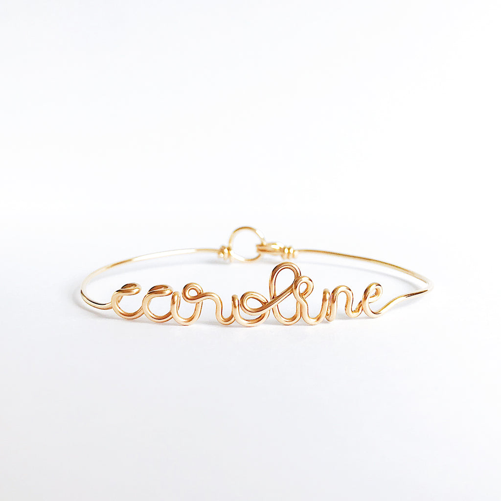 Personalised Caroline name wire bangle bracelet in Yellow Gold handmade by Rachel and Joseph jewellery UK