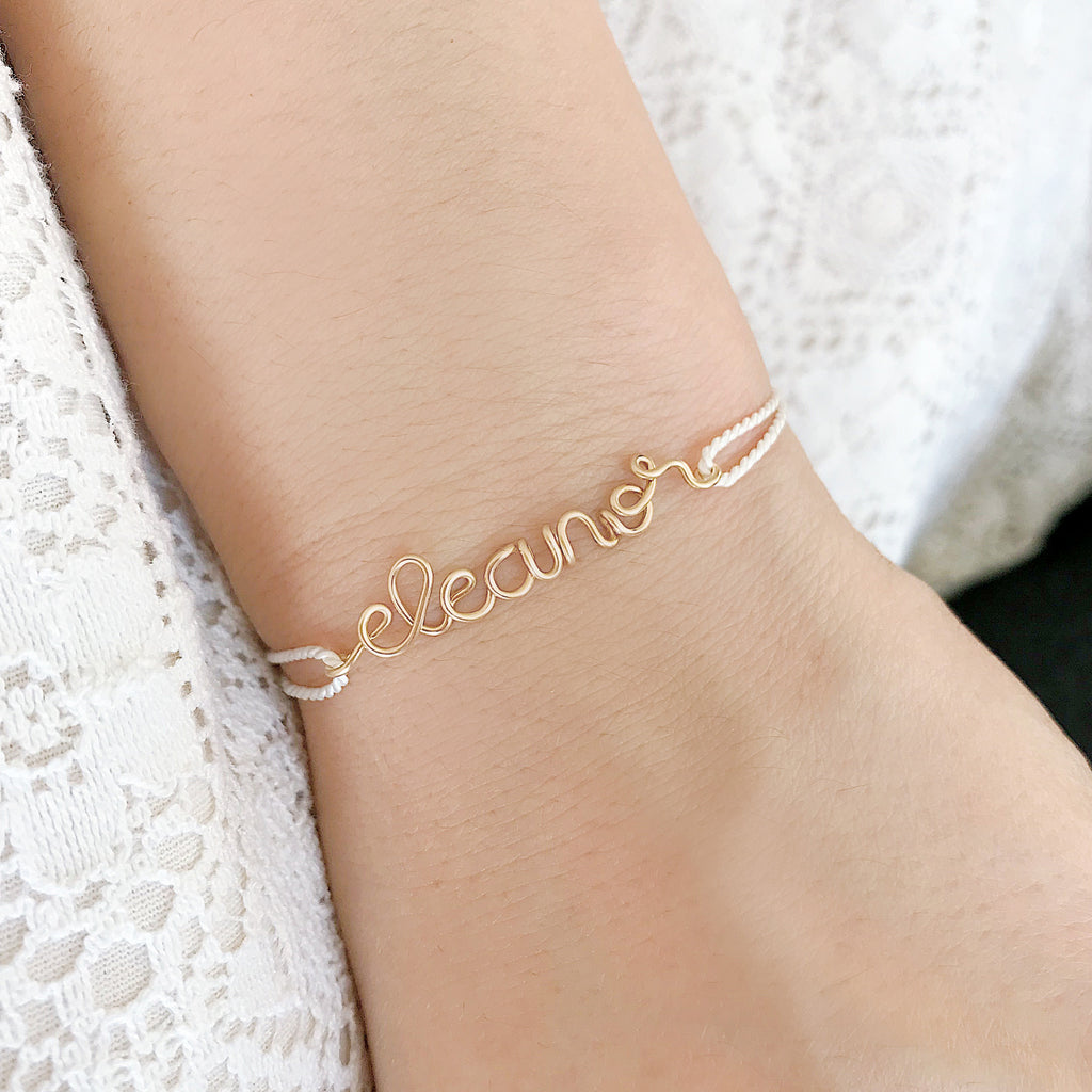 Personalised name Eleanor wire white natural Silk bracelet in 14K yellow gold filled handmade by Rachel and Joseph Jewellery in London, UK on wrist
