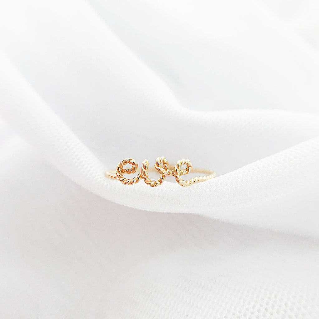 Personalised name Eve twisted wire ring 14K yellow gold filled handmade by Rachel and Joseph Jewellery in London, UK