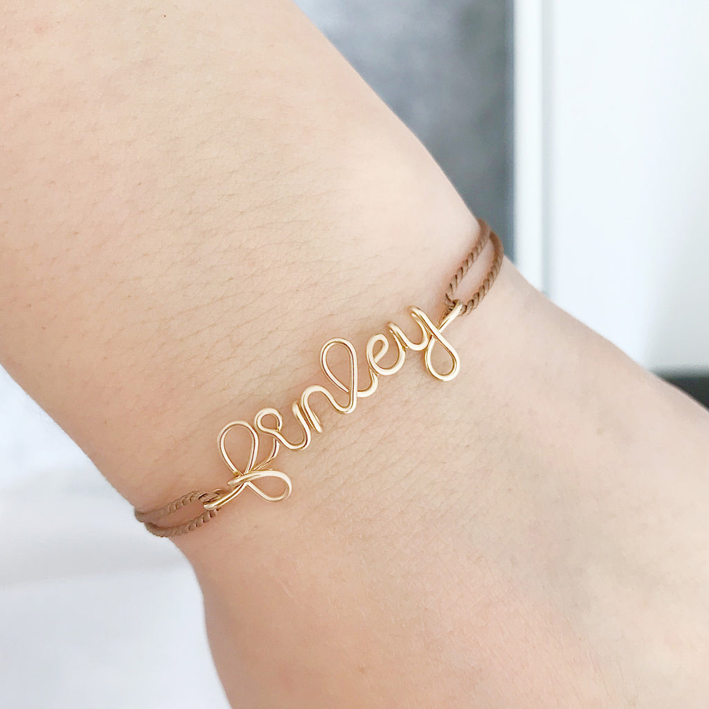 Personalised name Finley wire Beige natural Silk bracelet in 14K yellow gold filled handmade by Rachel and Joseph Jewellery in London, UK on wrist
