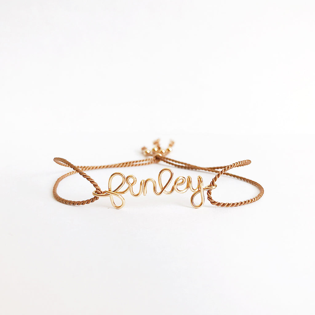 Personalised name Finley wire Beige natural Silk bracelet in 14K yellow gold filled handmade by Rachel and Joseph Jewellery in London, UK WB