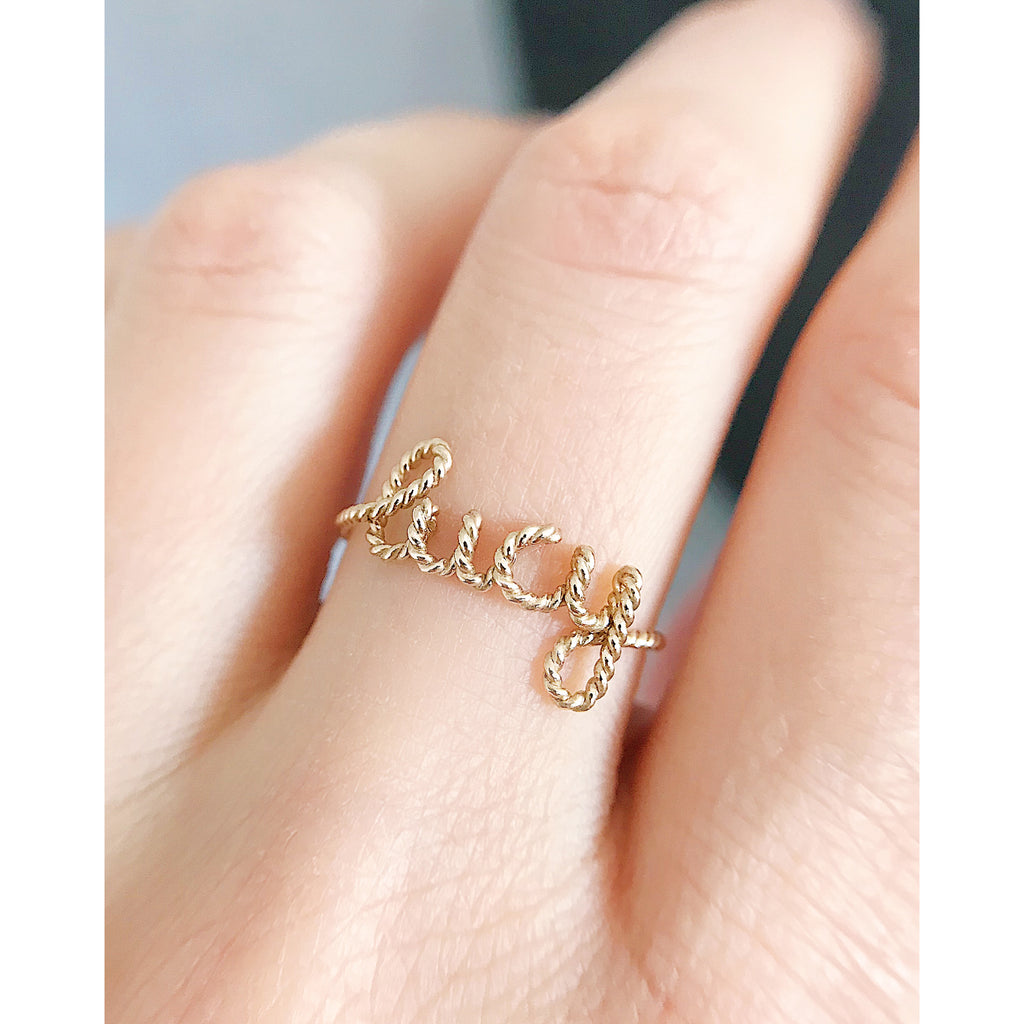 Personalised name Lucy twisted wire ring 14K yellow gold filled handmade by Rachel and Joseph Jewellery in London, UK hand
