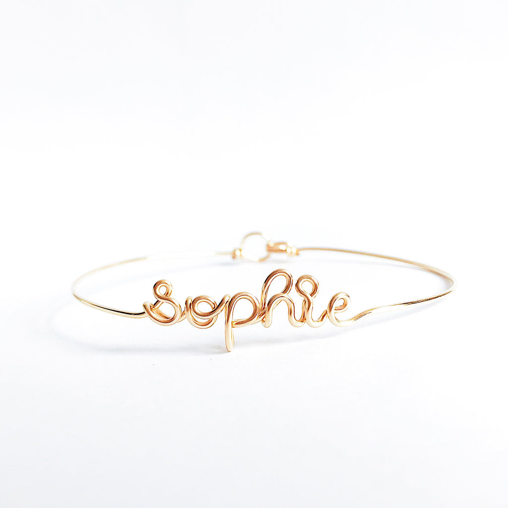 Personalised name Sophie wire bangle bracelet 14K yellow gold filled handmade by Rachel and Joseph Jewellery in London, UK