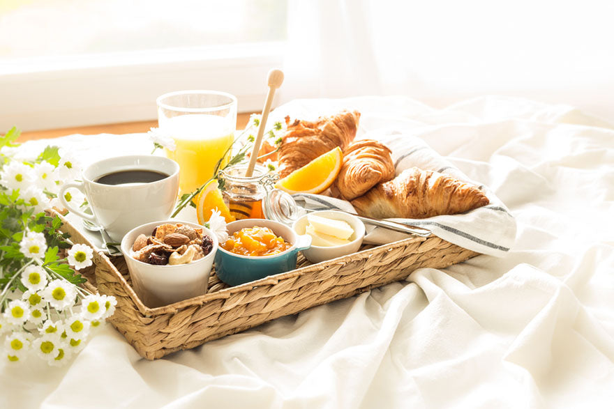 a tray of breakfast food on a bed