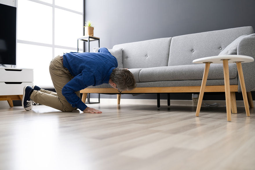 a man looking under a couch