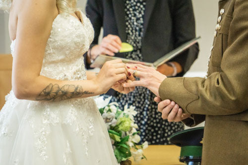 military wedding ring being placed