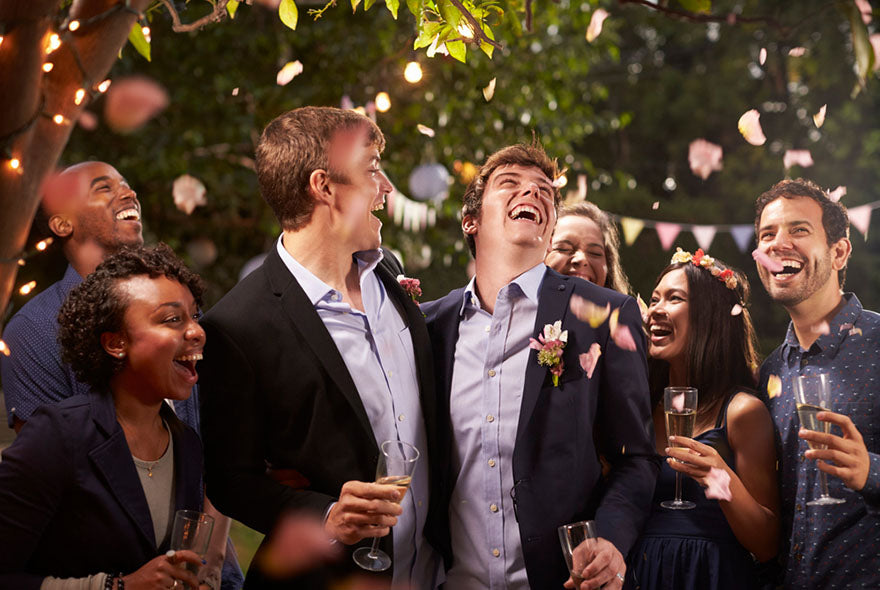pair grooms laughing at wedding reception
