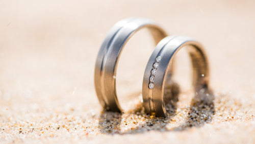 two wedding rings sand