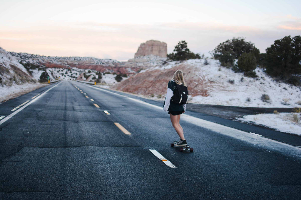 Girl skateboarding down a road in the desert