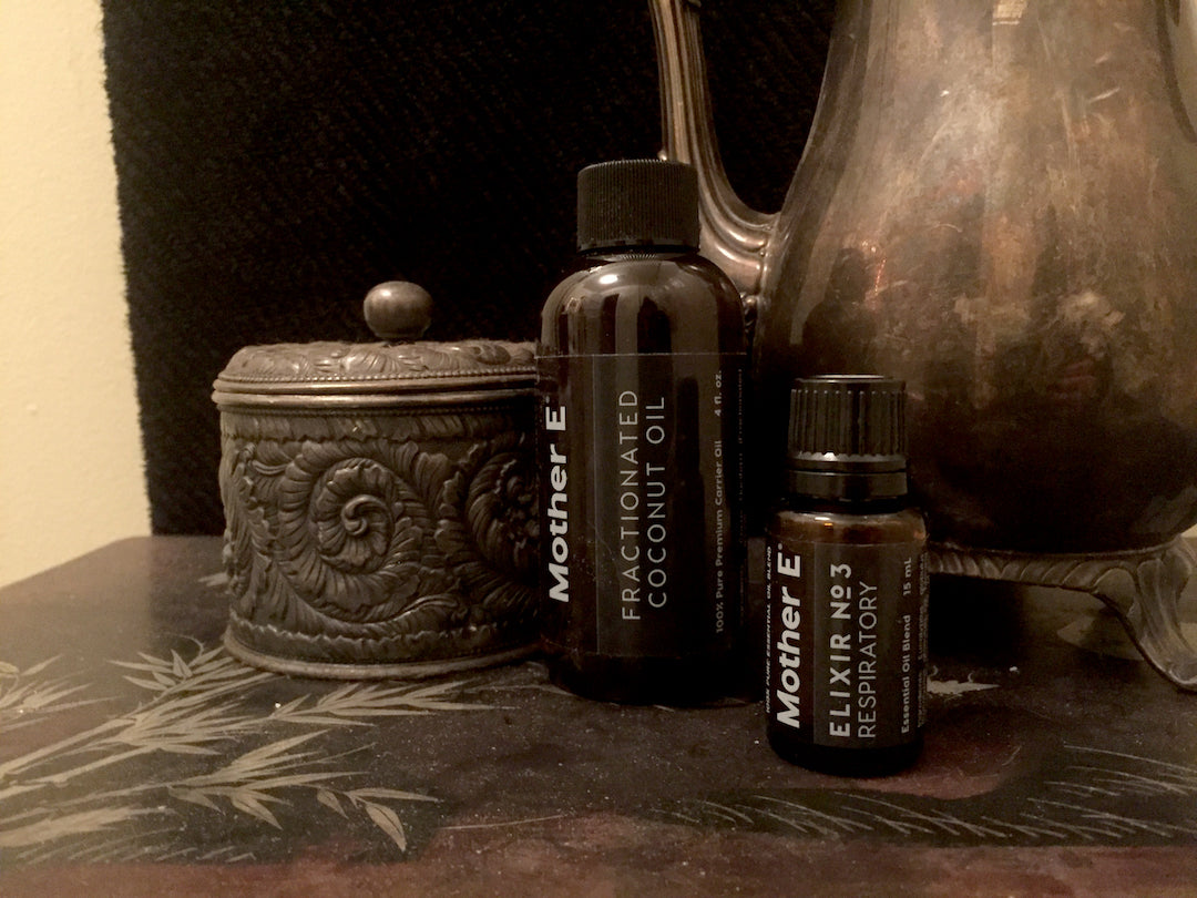 Elixir No 3 Respiratory with Fractionated Coconut Oil and some metal decor in front of a black towel in a bathroom